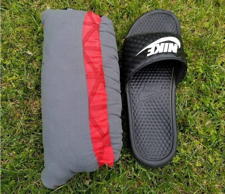 thermarest compressible backpackign pillow fully compressed side by side with a mens size 11 sandal