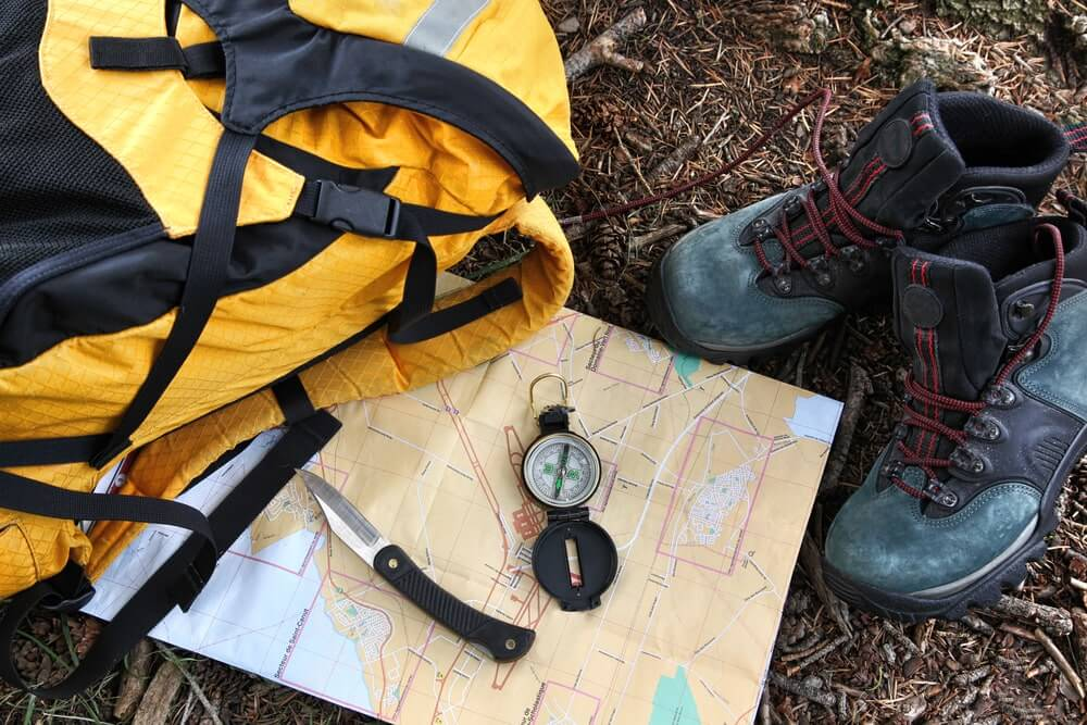 Hiking shoes on map with compass and a backpack