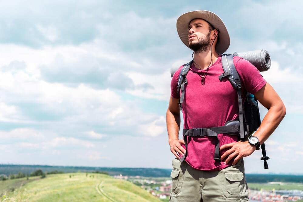 Handsome hiker in hat with backpack